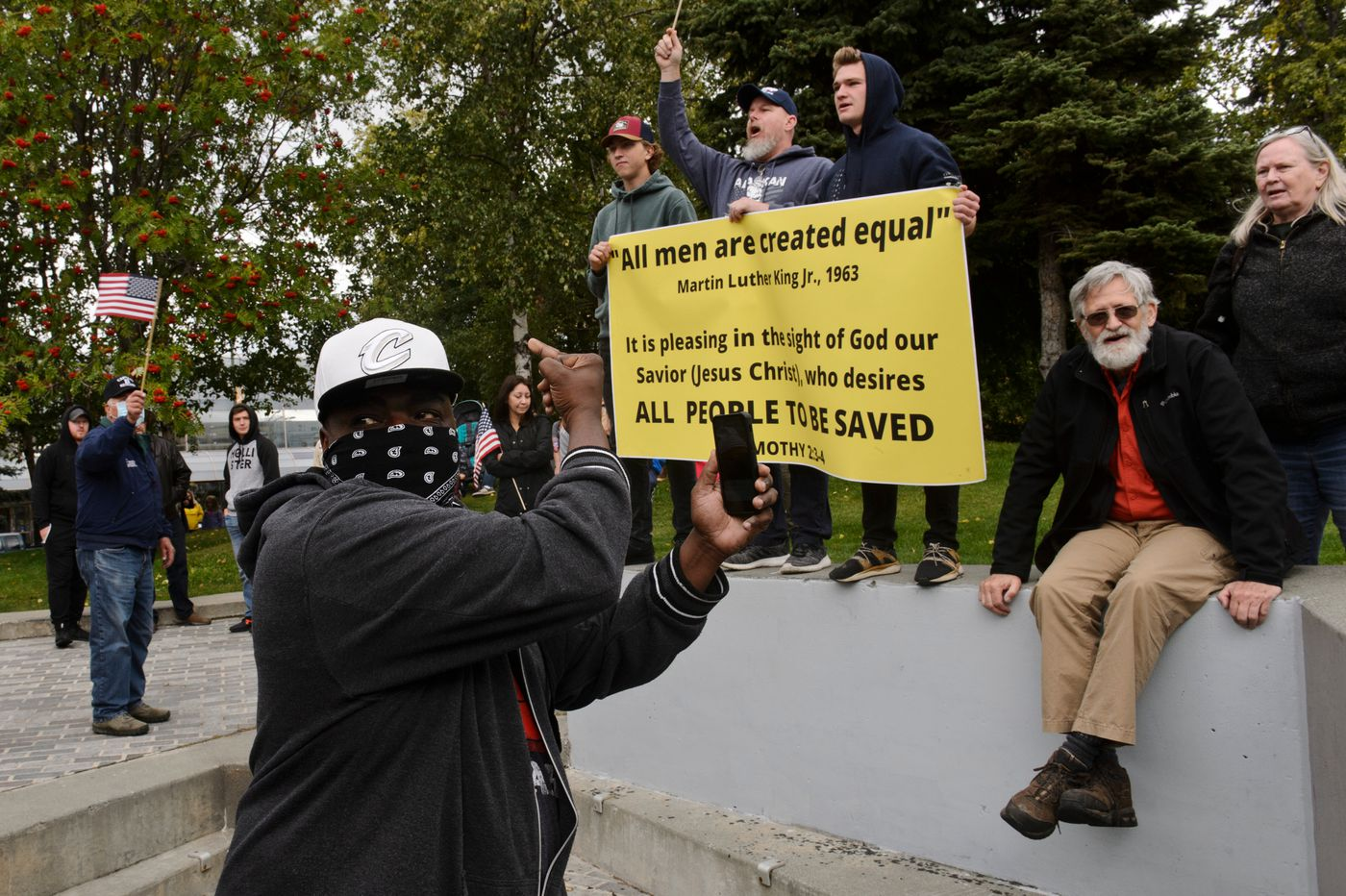 """A man gives a middle finger to counter-demonstrators at Town Square. The Alaska Black Caucus hosted the """"March on Alaska"""" in downtown Anchorage on Monday, September 7, 2020. The event supported racial equality, police accountability reform and the well-being of the Black community, according to organizers. (Marc Lester / ADN)"""