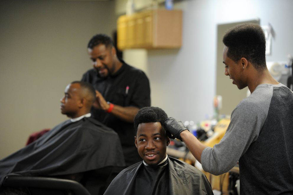 Anthony Squalls has his hair cut by Marcus Freeman at Unique Blends on Muldoon Road on Tuesday, Aug. 2, 2016, in Anchorage. In the background, shop owner Saeed McKoy cuts D-Neko Mason's hair. (Bob Hallinen / Alaska Dispatch News)