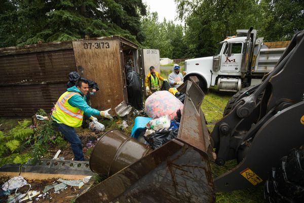 A crew from A-1 Lawn and Landscaping clears debris from a nuisance property at 11061 Gander St on Wednesday, Aug. 1, 2018. The municipality secured a court order to clean the property. (Loren Holmes / ADN)
