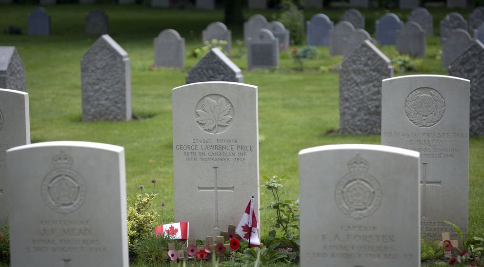 In this file photo taken on Saturday, July 26, 2014, wooden crosses and Canadian flags adorn the grave of World War I Canadian soldier Pvt. George Lawrence Price, center, at the St. Symphorien Cemetery near Mons, Belgium. Price was recorded as the last Canadian soldier to die on the Western Front during the First World War. (AP Photo/Virginia Mayo, File)