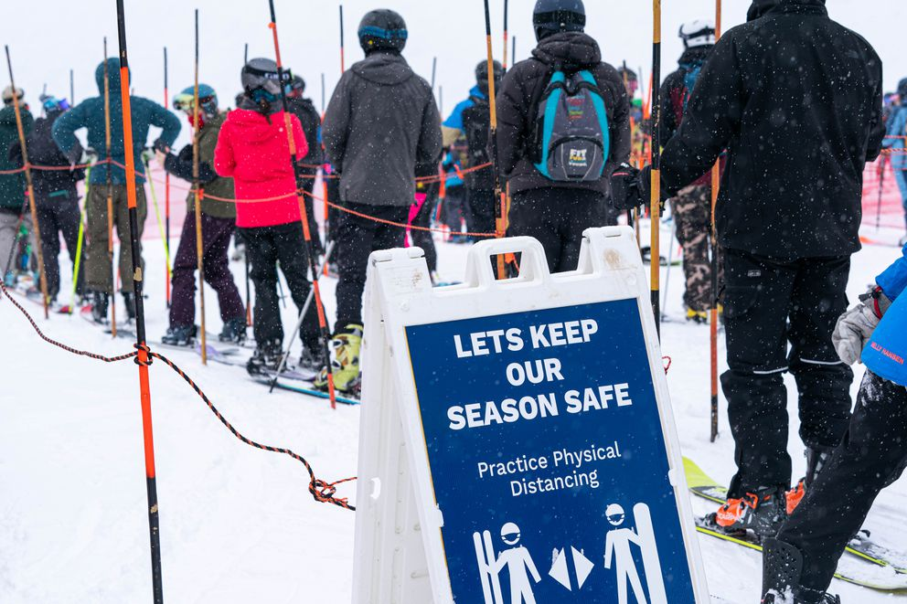 A sign reminds skiers and snowboarders to maintain physical distance in a lift line. (Loren Holmes / ADN)