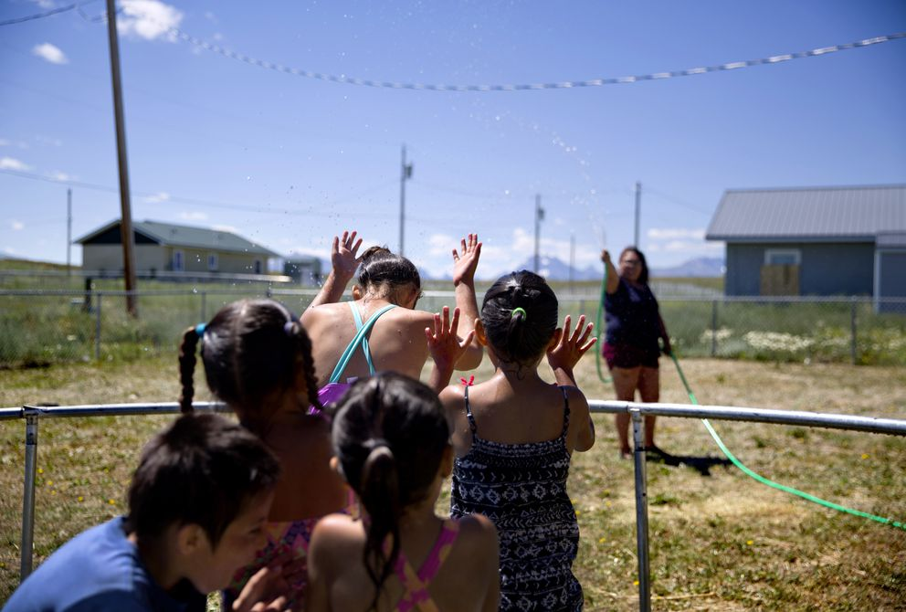 Tyisha ArrowTop Knot, right, sprays her nieces and nephews with a garden hose while looking after them in the backyard of their home on the Blackfeet Indian Reservation in Browning, Mont., Thursday, July 12, 2018. 'We've always been a cautious family, ' she said of watching out for the children in light of recent disappearances of Native American women. 'The world is just getting worse. ' (AP Photo/David Goldman)