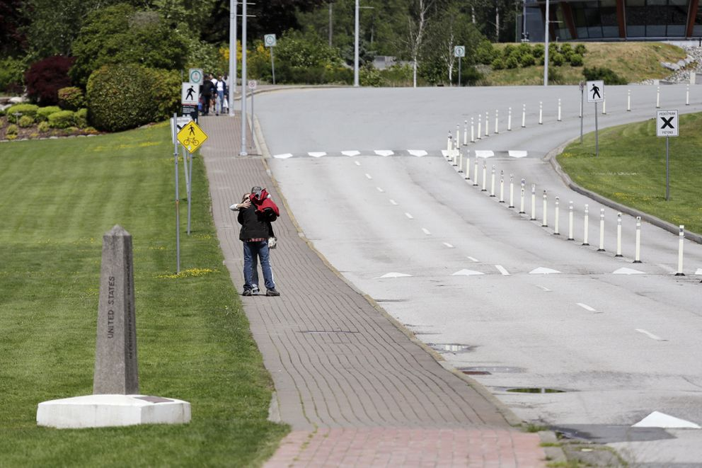 In this photo taken May 17, 2020, two people embrace after meeting at the border between the U.S. and Canada at Peace Arch Park, where traffic is almost nonexistent, in Blaine, Wash. (AP Photo/Elaine Thompson)