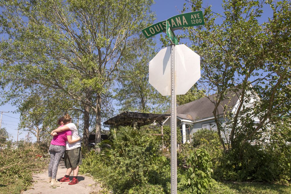 Adam Butler, 17, hugs his girlfriend, Eowyn Greene, 16, while standing on Louisiana Street in Lake Charles, La., as they and their families clean up their yards and houses following Hurricane Delta on Saturday, Oct. 10, 2020. (Chris Granger/The Advocate via AP)