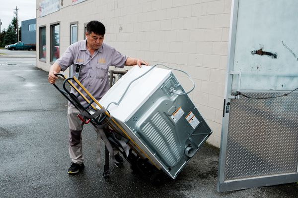 Chun B. Park loads a dryer unit back onto a handtruck after verifying that is is working correctly. (Young Kim / Alaska Dispatch)