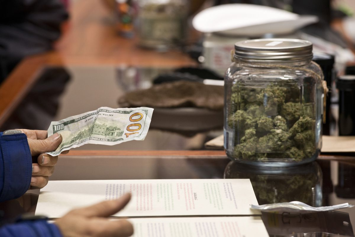 A customer pays for a purchase at Herbal Outfitters in Valdez on its opening day. (Marc Lester / ADN)