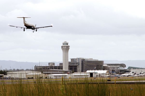 FILE - In this July 13, 2014, file photo, a plane lands at Portland International Airport in Portland, Ore. (AP Photo/Don Ryan, File)