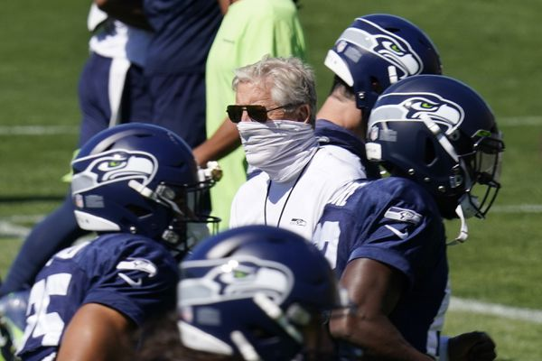 Seattle Seahawks head coach Pete Carroll, center, looks on as players run past Sunday, Aug. 30, 2020, during an NFL football training camp in Renton, Wash. (AP Photo/Elaine Thompson)