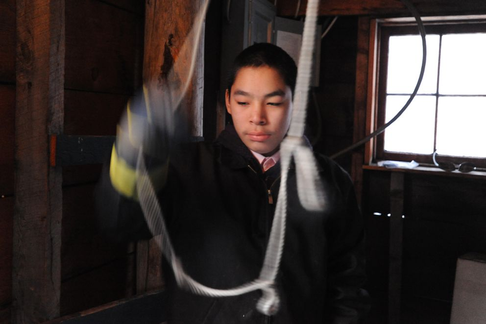 Star boy Sherman Kelila, 13, rings the bell at the Orthodox church in Aniak as parishioners celebrate Slaviq with starring and caroling on Monday. (Bill Roth / Alaska Dispatch News)