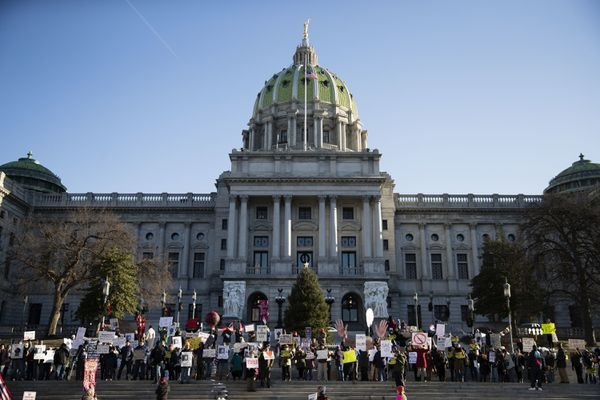 FILE—In this file photo from Dec. 19, 2016, protesters demonstrated ahead of Pennsylvania's 58th Electoral College at the state Capitol in Harrisburg, Pa. In 2016, the 20 unbound Electoral College members from Pennsylvania gathered in Harrisburg for Republican President-elect Donald Trump under pressure from Democrats to flip their vote to Democrat Hillary Clinton. This year, the 20 unbound Electoral College members from Pennsylvania will gather Monday, Dec. 14, 2020 in Harrisburg for Democratic President-elect Joe Biden, amid efforts by Trump to reverse the election result. (AP Photo/Matt Rourke, File)