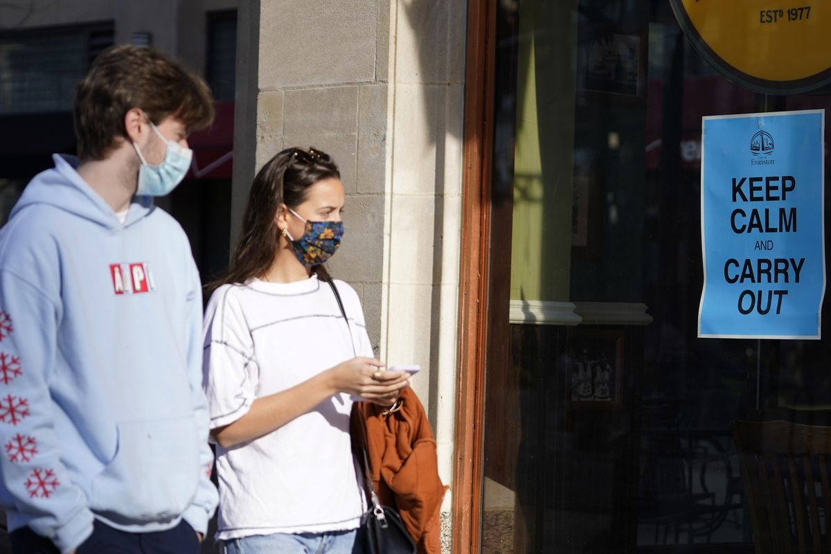 Pedestrians wear face masks as they pass a restaurant in downtown Evanston, Ill., Nov. 6, 2020. (Nam Y. Huh / AP)