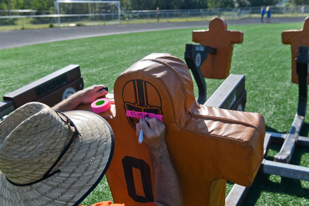 West assistant coach Zach Fleming writes a player's name on a sled pad because players aren't allowed to share equipment. (Marc Lester / ADN)
