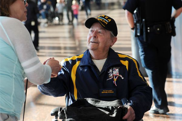 Korean War Navy veteran Howard Newman is thanked for his service by passersby Vivianne LeDoux prior to boarding the Last Frontier Honor Flight on Tuesday, April 18, 2017, at Ted Stevens Anchorage International Airport. (Erik Hill / Alaska Dispatch News)