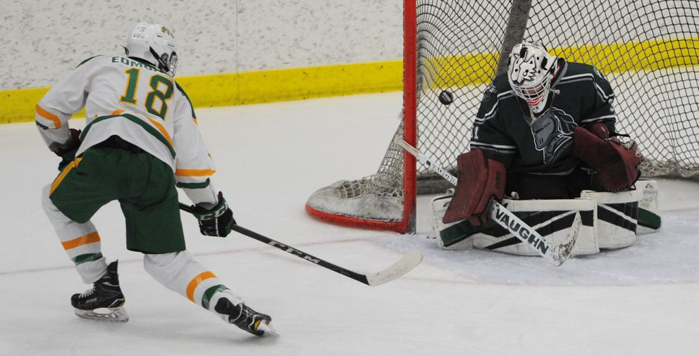 Service junior forward Brent Edmondson slips the puck past Colony goalie Roman Shepard. (Bill Roth / ADN)