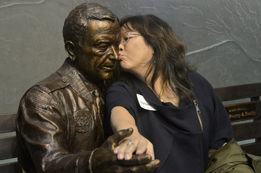 The statue of Ted Stevens gets a peck on the cheek from Katherine Gottlieb. (Marc Lester / ADN)