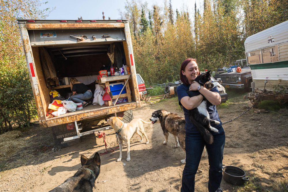 Ashley Johnson holds one of her cats around outside her temporary home, a box truck parked in a friend's yard, on Wednesday, Aug. 21, 2019 in Meadow Lakes. Johnson and her family lost their home in the McKinley Fire. (Loren Holmes / ADN)