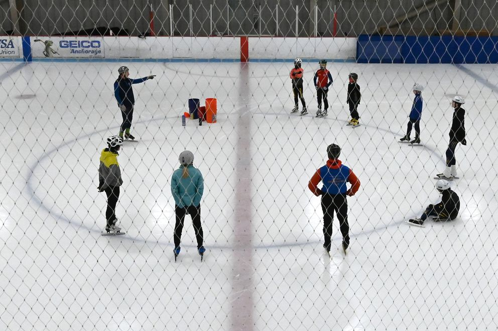 Speedskaters listen to instruction during Wednesday's practice. (Bill Roth / ADN)
