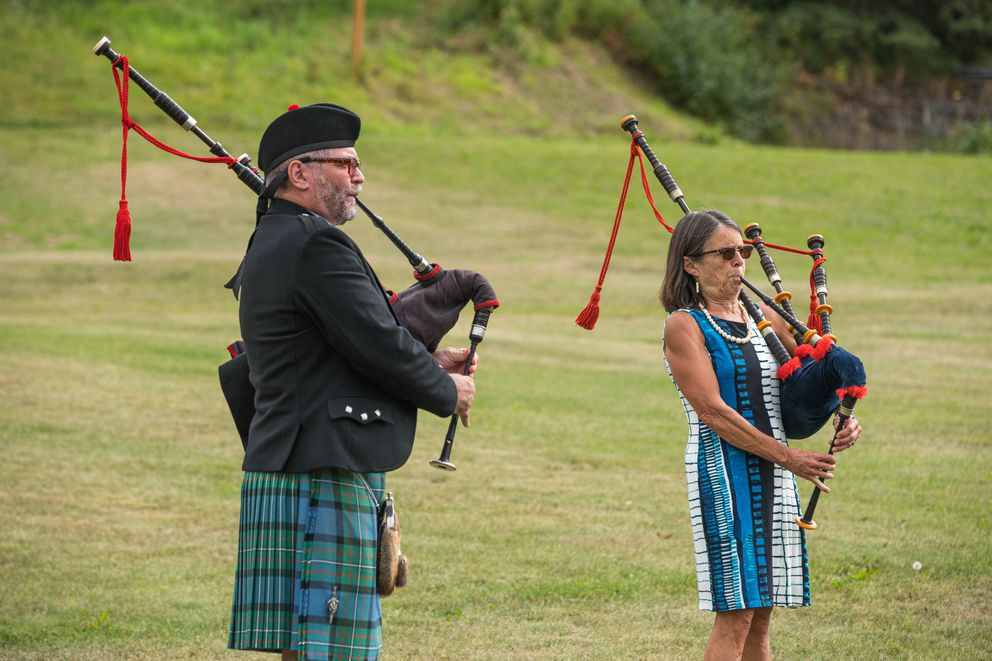 Ian White and Rep. Jennifer Johnston play the bagpipes Thursday, Aug. 15, 2019 during a celebration of life for Chris Birch at Hilltop Ski Area. (Loren Holmes / ADN)