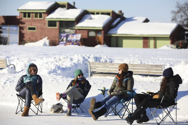 From left, Hanna Chastain, Sarah Fischer, Brooke Shortridge and Brooke Marston sit in the sun outside next to the Park Strip in downtown Anchorage and talk on Saturday, March 13, 2021. (Emily Mesner / ADN)