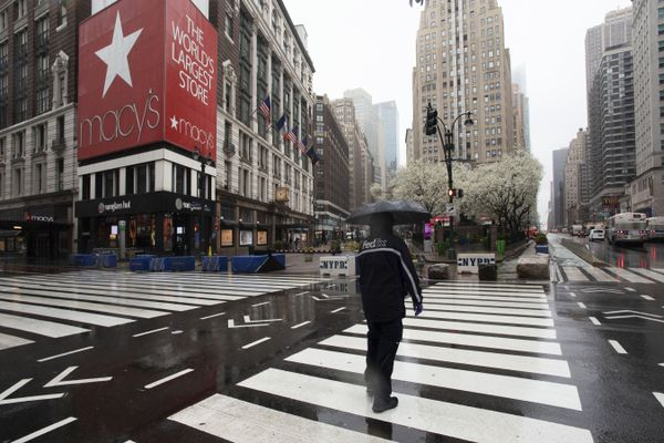 FILE - In this Monday, March 23, 2020 file photo, a man crosses the street in front of Macy's, in New York. Macy's is furloughing most of its 130,000 workers beginning this week as its sales have collapsed because of the coronavirus pandemic. The company said Monday, March 30 that it will be moving to an ''absolute minimum workforce