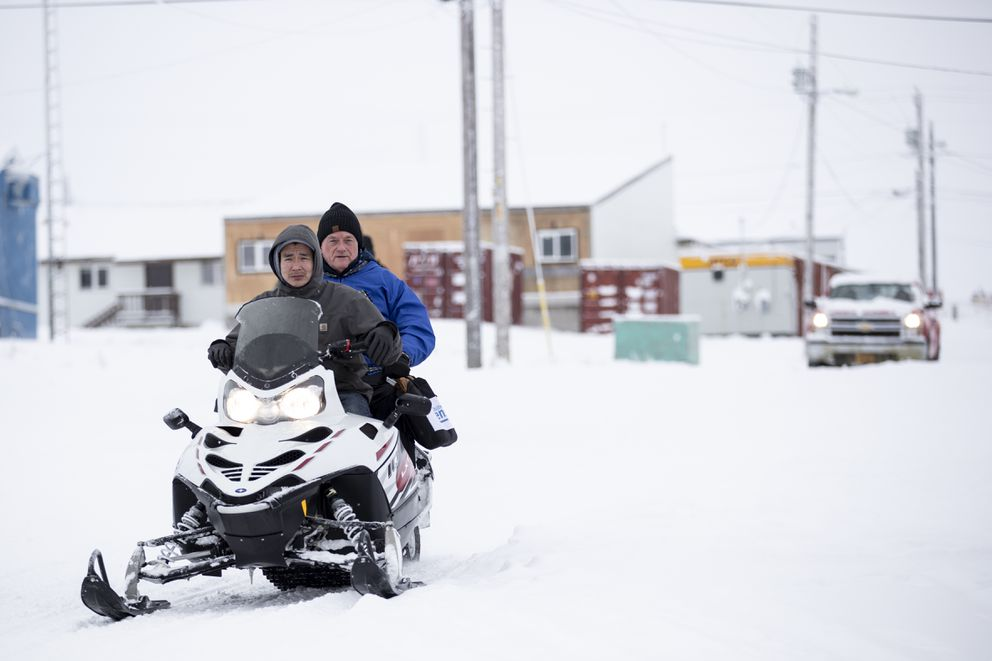 Census bureau director Steven Dillingham, center in blue jacket, rides behind Dennis Kashatok, left, as they arrive to conduct the first enumeration of the 2020 Census Tuesday, Jan. 21, 2020, in Toksook Bay, Alaska. (AP Photo/Gregory Bull)