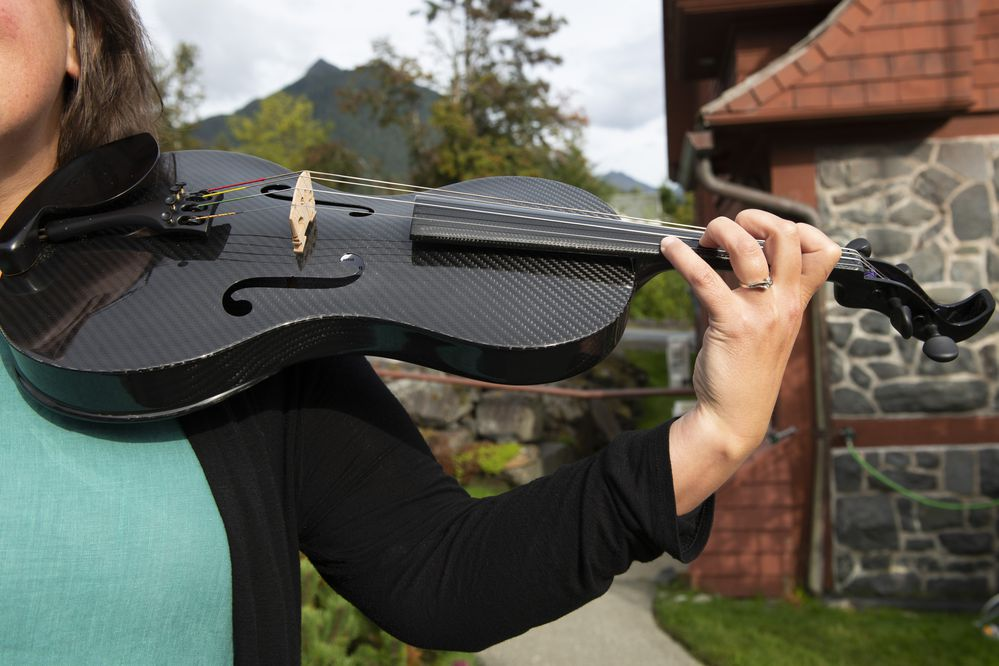 Sitka Summer Music Festival Executive Director Kayla Boettcher holds one of the festival's carbon fiber instruments at St. Peter's-by-the-Sea Episcopal Church Thursday, September 5, 2019, in Sitka, Alaska. (Photo by James Poulson)