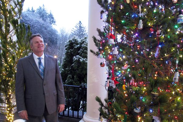 Alaska Gov. Mike Dunleavy looks up at a lit Christmas tree outside the governor's mansion on Tuesday, Dec. 11, 2018, in Juneau, Alaska. Dunleavy and his wife, Rose, hosted a holiday open house that doubled as an inaugural event. (AP Photo/Becky Bohrer)