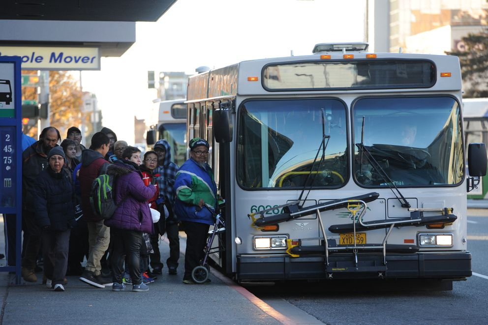 People board a bus at the Downtown Transit Center in Anchorage on Tuesday, Oct. 17, 2017. People Mover will launch a new bus system on Monday. (Bill Roth / Alaska Dispatch News)
