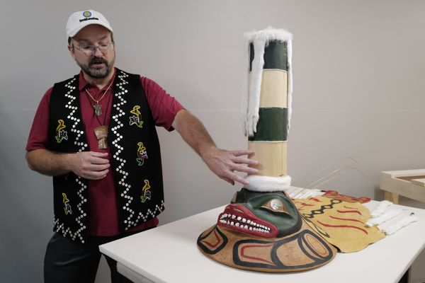 Eric Hollinger, Tribal Liaison for the Repatriation Office of the Smithsonian's National Museum of Natural History, talks about a sculpin clan hat replica before a welcoming ceremony at Elizabeth Peratrovich Hall on Wednesday, Sept. 25, 2019, in Juneau, Alaska. The original hat was collected from the Kiks.ádi Clan in Sitka in 1884. The Smithsonian Institution used a 3D digitization process to document the hat and construct the hat using traditional materials. (Michael Penn/The Juneau Empire via AP)