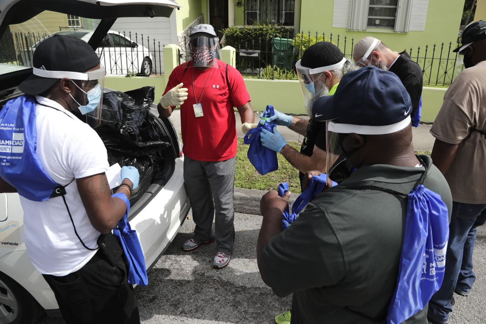 Morris Copeland, of the Strategic Urban Response to Guideline Education (SURGE) group, center, passes out kits to team members which they will distribute to residents living in COVID-19 hotspots, during the new coronavirus pandemic, Wednesday, July 1, 2020, in the Liberty City neighborhood of Miami. (AP Photo/Lynne Sladky)