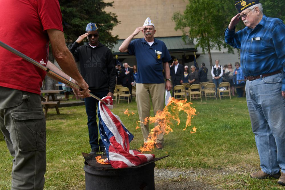 "Tim Campbell, left, puts a flag on the fire during a flag retirement ceremony. American Legion Jack Henry Post 1, on Fireweed Lane, hosted a U.S. flag retirement ceremony on Flag Day, June 14, 2019. Members retired dozens of flags that were in poor condition by burning them, the preferred method as instructed by the U.S Flag Code. Michael Downs, commander of Post 1, said American Legion Posts nationwide hosted similar ceremonies Friday, and it's a longstanding tradition for his Anchorage membership. ""That flag is why why we joined the military,"" Downs said. Members of the public drop off flags to be retired throughout the year. The Jack Henry Post, which will celebrate its 100th anniversary this year, also retired and placed the U.S flag from its own pole. (Marc Lester / ADN)"