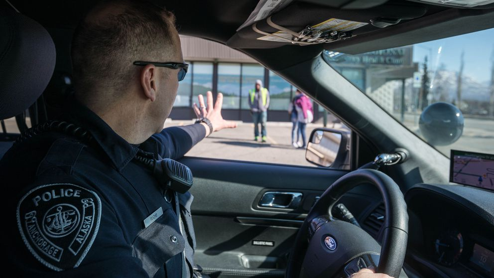Senior Patrol Officer Brian Fuchs waves to people on the sidewalk near Clark Middle School on Wednesday, April 3, 2019 in Mountain View. Fuchs is one of the officers now assigned to Mountain View, part of an Anchorage Police Department beat restructuring plan designed to create a more consistent and friendly presence in Anchorage neighborhoods. (Loren Holmes / ADN)