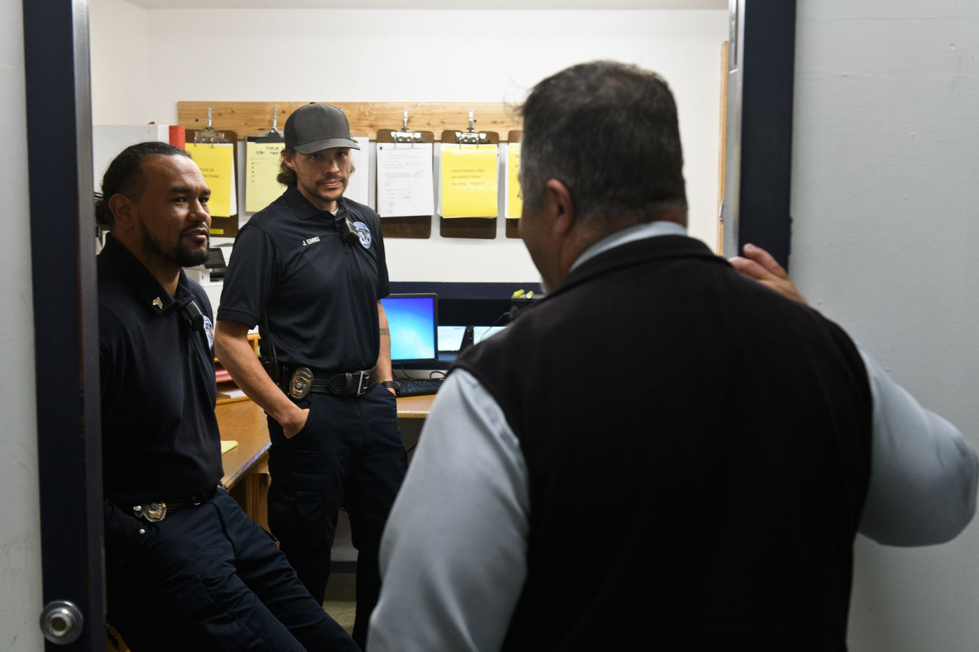 Correctional officers Benny Flores, left and Justin Ennis talk with Spring Creek superintendent Bill Lapinskas on Sept. 27. Ennis started a running club for prisoners at Spring Creek in April. (Marc Lester / ADN)
