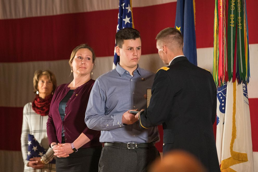 Col. Dave Zinn, the current commander of the brigade Staff Sgt. Justin Gallegos served in during the 2009 battle of Kamdesh, presents the Distinguished Service Cross to Gallegos' son MacAiden, on Saturday, Dec. 15, 2018 at the Frontier Theater on Joint Base Elmendorf-Richardson. Looking on is MacAiden's mother, Amanda Marr, and U.S. Senator Lisa Murkowski, who presented the family with a flag that had flown over the U.S. Capitol. (Loren Holmes / ADN)