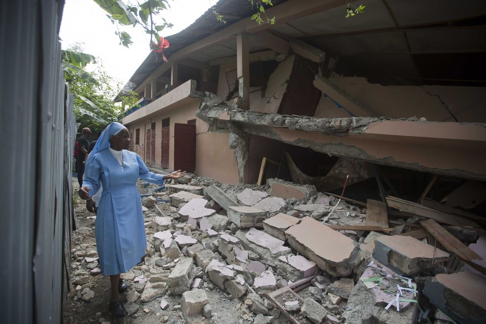 Sr Maryse Alsaint walks alongside a school damaged by a magnitude 5.9 earthquake the night before, in Gros Morne, Haiti, Sunday, Oct. 7, 2018. Emergency teams worked to provide relief in Haiti on Sunday after the quake killed at least 11 people and left dozens injured. ( AP Photo/Dieu Nalio Chery)