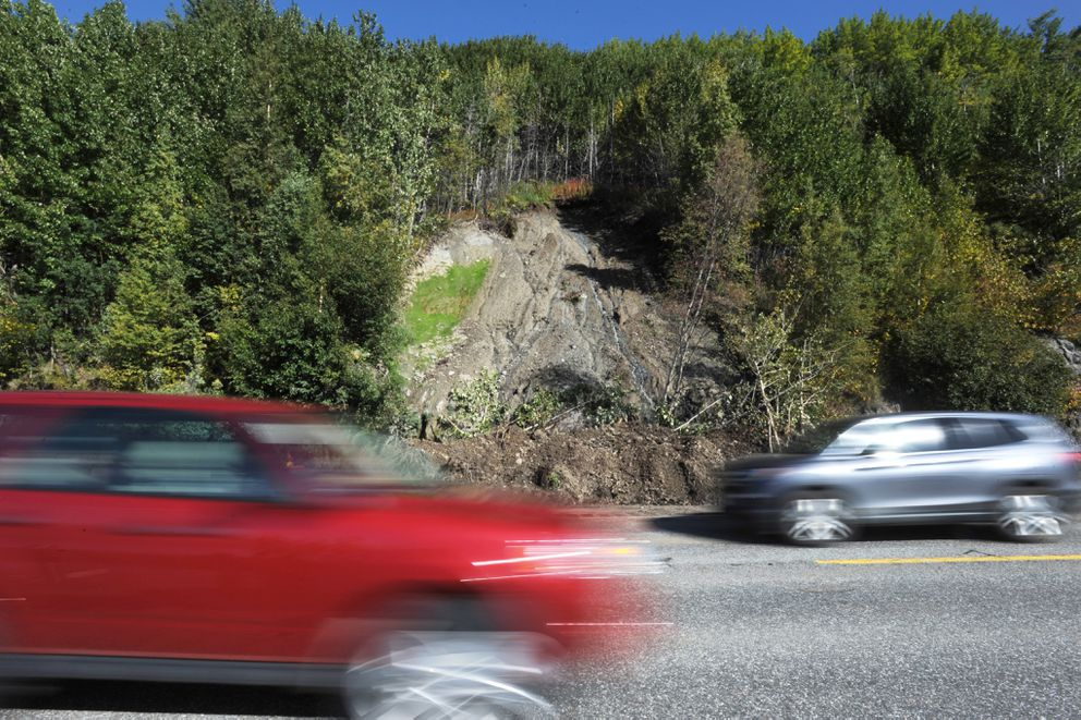 Motorists pass by landslide debris at Mile 105 of the Seward Highway on Sunday.  (Bill Roth / ADN)
