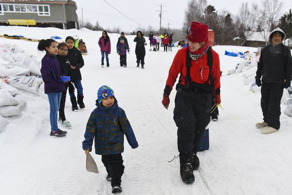 Musher Aliy Zirkle talks with children in Shageluk as she retrieves hot water during the Iditarod on March 8, 2019. (Marc Lester / ADN)
