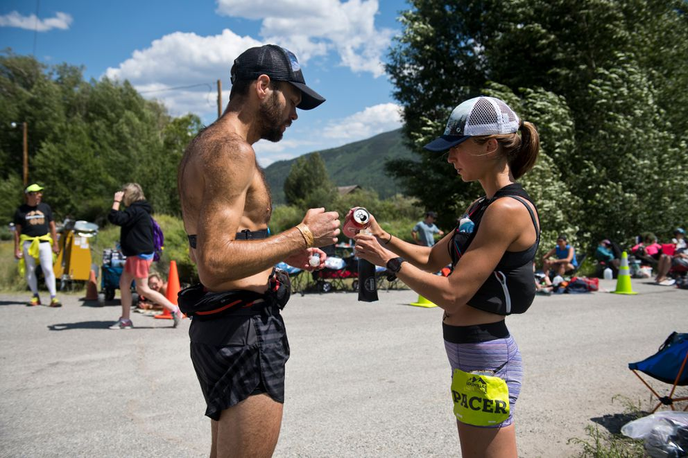 Anna Dalton fills bottles with Chad Trammell at an aid station at last summer's Leadville Trail 100 in Colorado. Dalton ran as a pacer for Trammell, who is one of her coaches, for a portion of the 100-mile run. (Marc Lester / ADN)