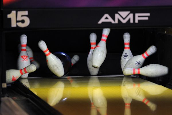 ERIK HILL / Anchorage Daily News Pins fly as a young bowler rolls a strike at the Sean Rash Stars of the Future bowling tournament Thursday Dec. 27, 2012 at Jewel Lake Bowl.