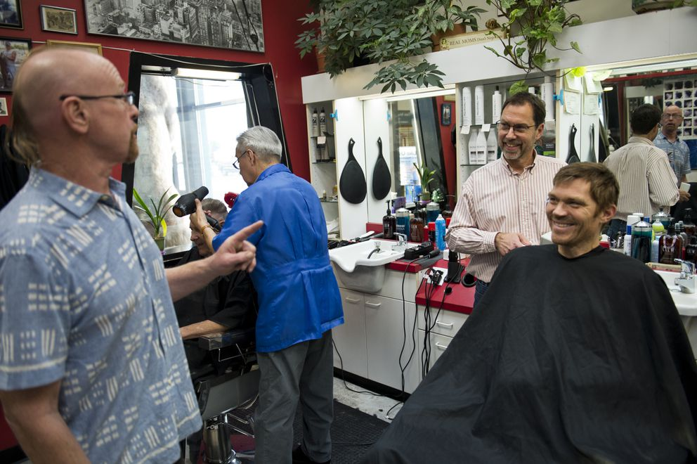 Scott Theis prepares to cut Mark Renner's hair and talks to other customers.. (Marc Lester / ADN)