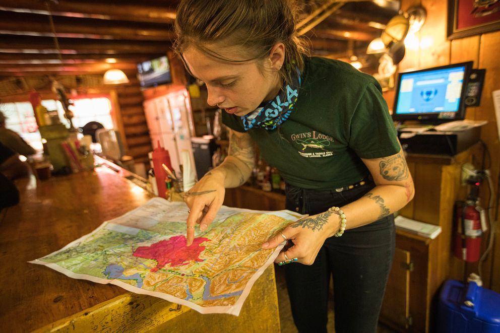 Bartender Kat Ross points at a map of the Swan Lake Fire Sunday, Aug. 18, 2019 at Gwin's Lodge in Cooper Landing. Ross said the staff has been filling in the map this summer as the fire has grown, and is concerned about it reaching the nearby Resurrection Pass, which it did this weekend. (Loren Holmes / ADN)
