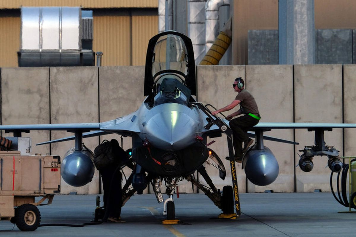 A mechanic climbs into the cockpit of an Air Force F-16 at Bagram Air Field in Afghanistan in August. (JOSH SMITH / Reuters)