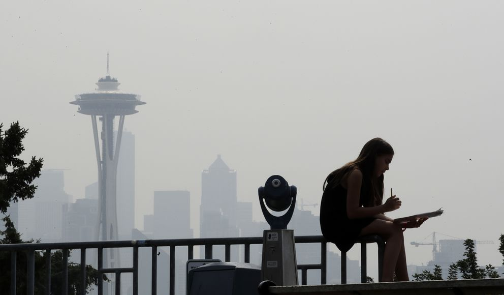 FILE - In this Aug. 14, 2018 file photo, a girl works on a drawing next to a viewing scope as a smoky haze obscures the Space Needle and downtown Seattle behind. (AP Photo/Elaine Thompson, File)