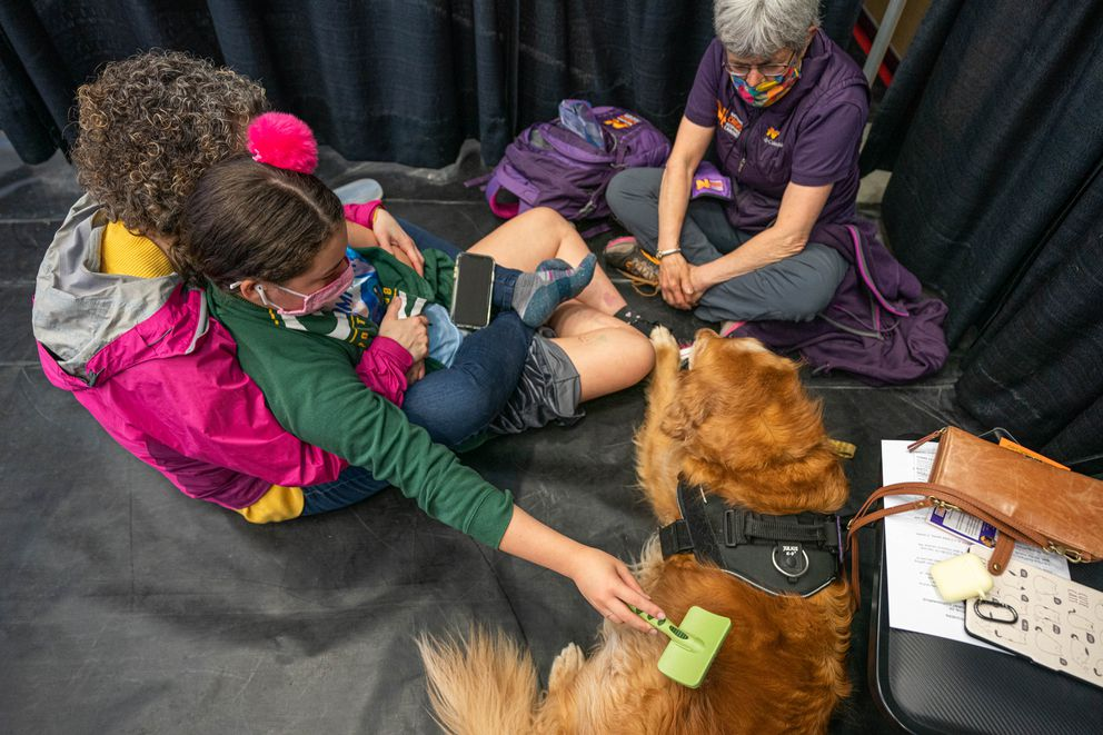 Lillian sits in her mom's lap and brushes Grover's fur before her shot. (Loren Holmes / ADN)