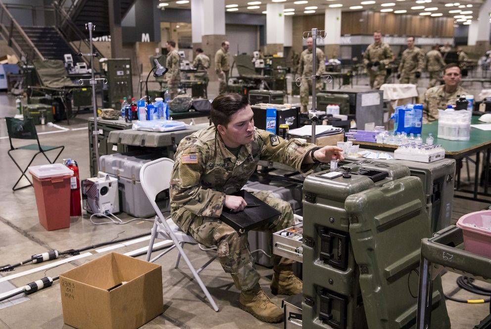 Nathaniel Castonguay, a licensed vocational nurse out of Fort Lewis, helps organize medical drawers as the Army sets up a field hospital for non-COVID-19 patients at CenturyLink Field Events Center in Seattle. (Amanda Snyder/Seattle Times/TNS)