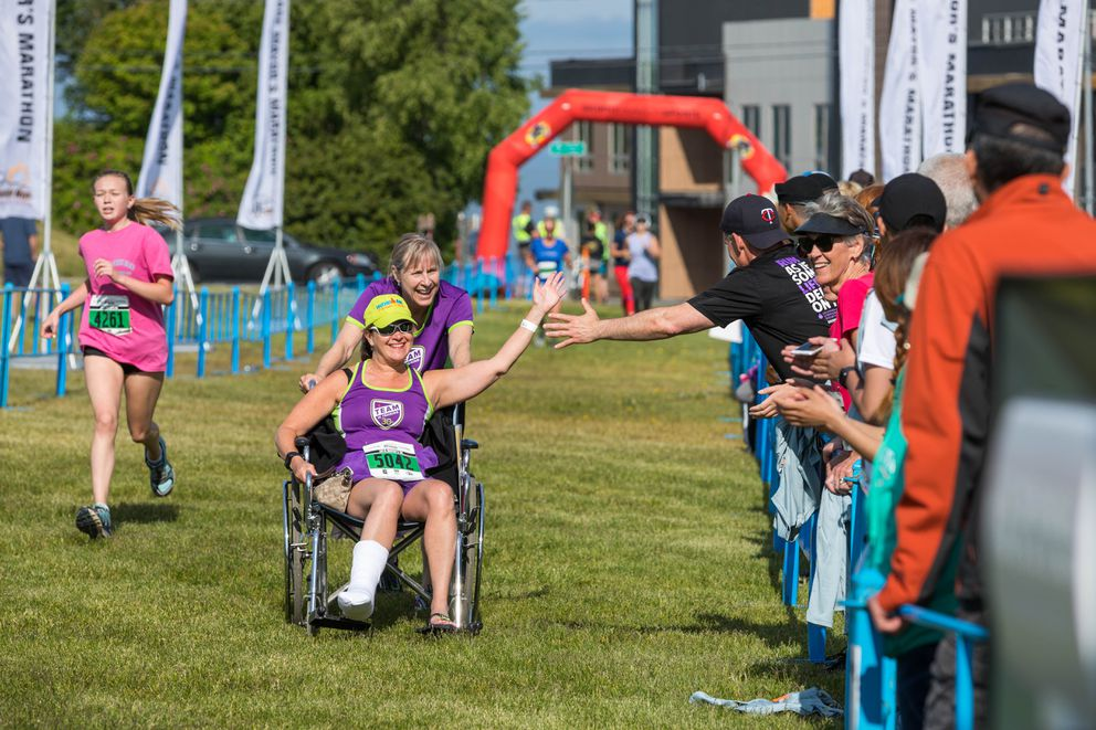 Shawn Wiski pushes a wheelchair carrying Denise Smieja toward the finish line. (Loren Holmes / ADN)