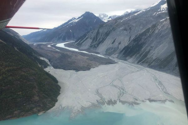 """The terminus of Lituya Glacier on September 17, 2020, after the delta (foreground gravels) was completely resurfaced by the Aug. 15 outburst flood. The source of the flood, """"Desolation Lake,"""" is just visible under the aircraft's red pitot tube, while the main body of Lituya Glacier emerges from the mountains to the right. (Photo courtesy of J. Capra/NPS)"""