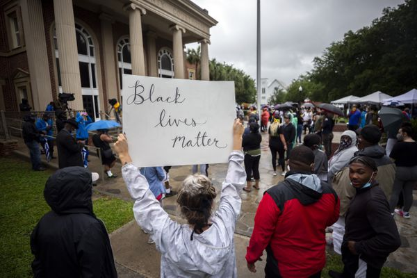 A group of protesters gather outside the Glynn County Courthouse while a preliminary hearing is being held inside for for Travis McMichael, Gregory McMichael and William Bryan, Thursday, June 4, 2020, in Brunswick, Ga. The three are accused of shooting of Ahmaud Arbery while he ran through their neighborhood in February. (AP Photo/Stephen B. Morton)