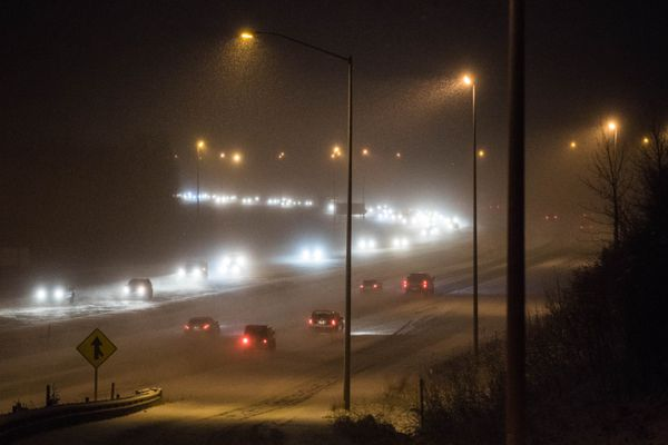 Morning traffic moves along the Glenn Highway early Thursday morning, Nov. 16, 2017. Snow was falling across the Anchorage area, with up to two inches forecast. (Loren Holmes / Alaska Dispatch News)
