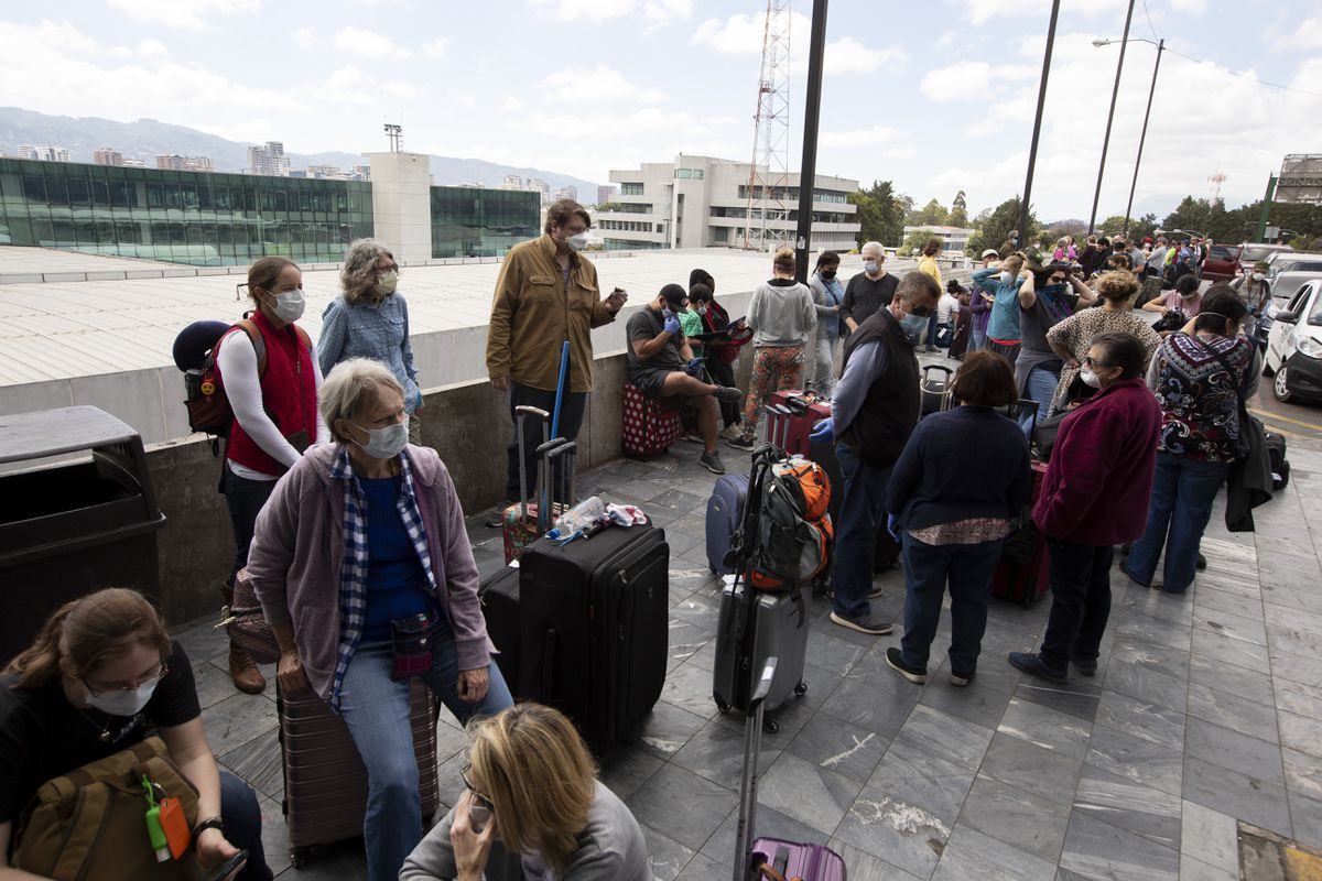 Travelers wait to take a charter flight coordinated by the U.S. embassy at La Aurora airport in Guatemala City, Monday, March 23, 2020. American citizens stranded abroad because of the coronavirus pandemic are seeking help in returning to the United States. (AP Photo/Moises Castillo)
